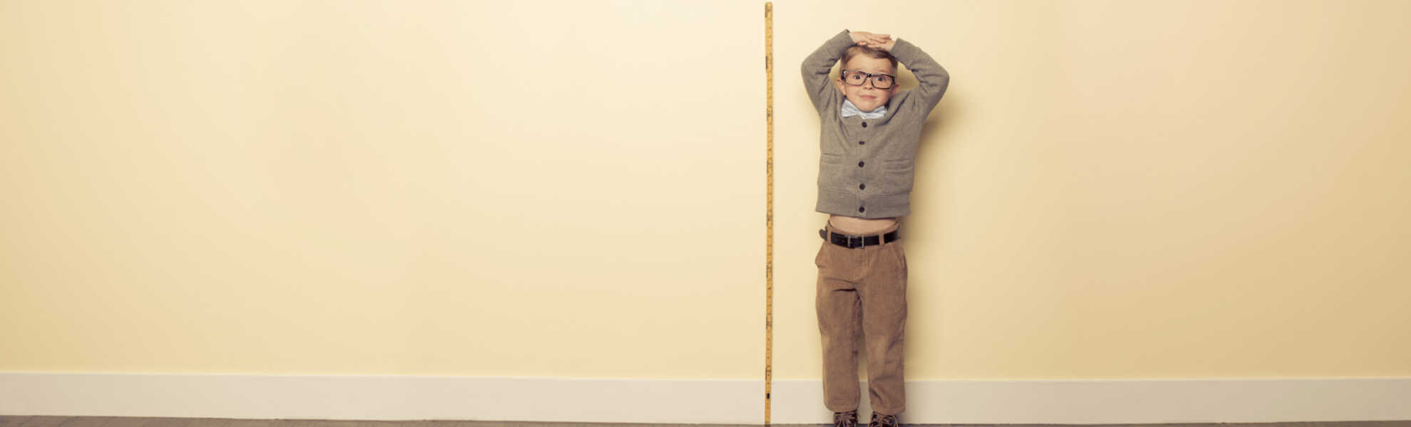 A child measuring height to see if he has grown taller